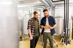 Люди с доской сзажимом для бумаги на винзаводе ремесла или заводе пива Стоковые Фото