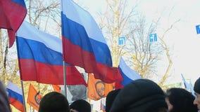 Люди с русскими tricolor флагами и ленты на марше памяти убитого лидера оппозиции Бориса Nemtsov