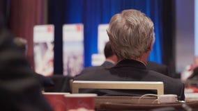 Люди слушают на конференции видеоматериал