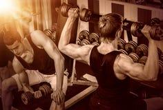 Люди с штангой на спортзале Предпосылка тона цвета Стоковая Фотография RF