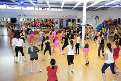Люди танцуя во время фитнеса тренировки Zumba на спортзале Стоковое Фото