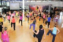 Люди танцуя во время фитнеса тренировки Zumba на спортзале Стоковое фото RF