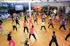 Люди танцуя во время фитнеса тренировки Zumba на спортзале Стоковое Изображение RF