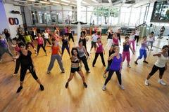 Люди танцуя во время фитнеса тренировки Zumba на спортзале Стоковое Изображение