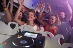 Люди танцуя в ночном клубе с DJ в переднем плане стоковое фото rf