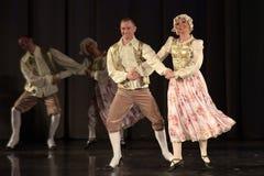 Люди танцуя в традиционных костюмах на этапе, Стоковые Фото