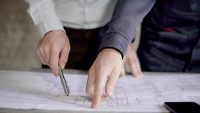 Люди урожая обсуждая светокопию Безликая съемка подрядчика и построителя работая на светокопии нового здания и акции видеоматериалы