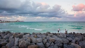Люди удя на заходе солнца на Miami Beach видеоматериал