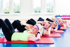 Люди фитнеса в спортзале делая хрусты Стоковая Фотография