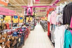 Люди ходя по магазинам для дешевых одежд в магазине супермаркета стоковые изображения
