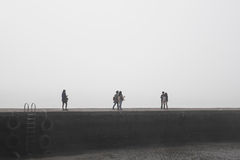 Люди шли безцельно с загадочным туманом на дамбе на порте Стоковые Изображения RF