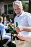 Люди clinking пивные бутылки на пикнике Стоковые Фотографии RF