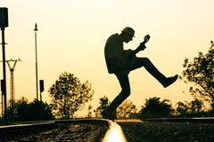 Люди jumpig на следе с гитарой в средний-воздухе стоковая фотография rf