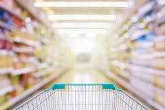 Магазинная тележкаа в предпосылке нерезкости междурядья супермаркета Стоковое Фото