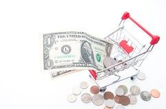 Магазинная тележкаа при банкноты и монетки долларов изолированные на белизне Стоковая Фотография
