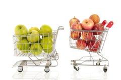 Магазинная тележкаа с зелеными и красными яблоками Стоковое Фото