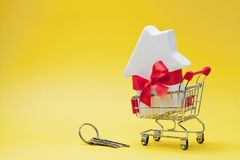 Магазинная тележкаа с малым Белым Домом украсила красные ленту смычка и пук ключей на желтой предпосылке Покупать новый дом, пода стоковое изображение