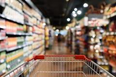 Магазинная тележкаа с предпосылкой нерезкости междурядья супермаркета Стоковая Фотография RF