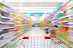Магазинная тележкаа с предпосылкой нерезкости междурядья супермаркета Стоковое фото RF