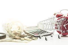 Магазинная тележкаа с монетками и банкнота доллара на белой предпосылке Стоковые Фото