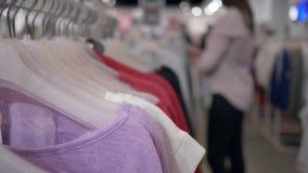 Магазин одежды, модная новая одежда вися на вешалках и женщина покупателя в несосредоточенной предпосылке выбирают приобретения в видеоматериал