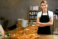 Магазин печенья Портрет молодой женщины работая в хлебопекарне стоковые фото