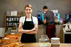 Магазин печенья Портрет молодой женщины работая в хлебопекарне стоковое изображение