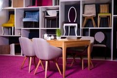 Магазин, продажа мебели в торговом центре Образец экспозиции обедая деревянный стол с стульями ткани в сером цвете на белой полке Стоковая Фотография RF