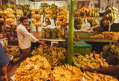 Магазин с бананами и плодоовощами людей покупая на рынке фермеров Стоковая Фотография