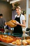 магазин хлебопекарни Счастливая женщина продавая печенье стоковое фото rf