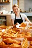 магазин хлебопекарни Счастливая женщина продавая печенье стоковые изображения