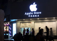 Магазин Яблока в Китае будучи закрыванным с силуэтами passersby Стоковые Фото