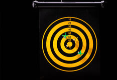 Магнитные стрелки дротика на желтой доске дротика Черная предпосылка Стоковые Фото