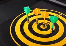 Магнитные стрелки дротика на желтой доске дротика Черная предпосылка Стоковые Изображения