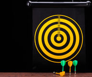 Магнитные стрелки дротика на поверхности гранита и предпосылке доски дротика Стоковые Фото