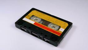 Магнитофонная кассета вращает на белой предпосылке видеоматериал