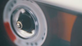 Магнитофонная кассета в магнитофоне играя и вращает сток-видео