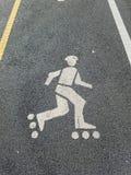 Майна кататься на коньках ролика на пути велосипеда, с желтыми и белыми линиями раздела стоковое изображение