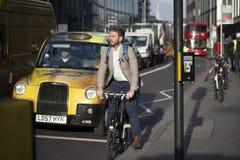 Майна кирпича улицы в полдень в backlight Спешность людей о их деле Человек ехать велосипед на дороге Восточный Лондон стоковые фото