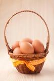 Май eggs в меньшей корзине с желтым смычком на деревянной таблице Стоковая Фотография RF