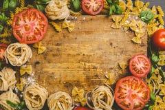 Макаронные изделия и овощи разбросанные вокруг разделочной доски Стоковые Фотографии RF