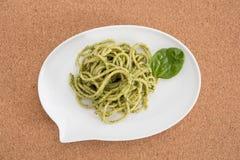 Макаронные изделия спагетти с соусом песто в белом блюде в форме пузыря болтовни, на предпосылке пробочки Стоковое Изображение