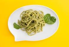 Макаронные изделия спагетти с соусом песто в белом блюде в форме пузыря болтовни, на яркой желтой предпосылке Стоковые Фотографии RF