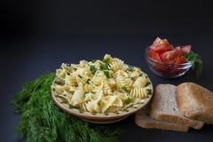 Макаронные изделия с зеленым укропом, отрезанными томатами и хлебом стоковое фото rf