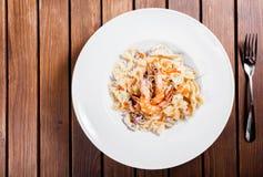Макаронные изделия с морепродуктами, креветкой, мидиями, осьминогом, устрицами, травами и cream соусом на деревянной предпосылке стоковые изображения