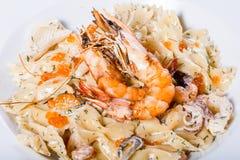Макаронные изделия с морепродуктами, креветкой, мидиями, осьминогом, устрицами, травами и cream соусом на деревянной предпосылке стоковые фото