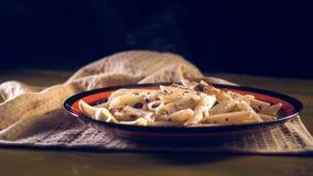 Макаронные изделия с семенить мясом, чесноком и луком в военно-морск-стиле на желтом деревянном столе Makarony po-flotski, русско стоковое изображение