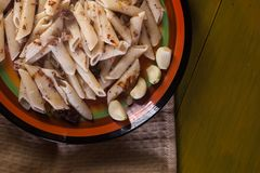 Макаронные изделия с семенить мясом, чесноком и луком в военно-морск-стиле на желтом деревянном столе Makarony po-flotski, русско стоковые изображения