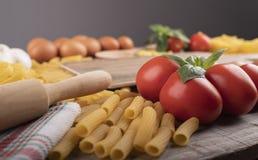 Макаронные изделия, томаты и ингредиенты для итальянского ресторана с деревянной тестомесилкой стоковые фото