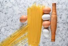Макаронные изделия, яичка, свертывая на белой конкретной поверхности Варочный процесс, ингридиенты и инструменты кухни столового  Стоковые Фотографии RF